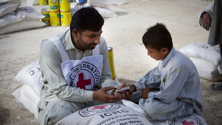 Boy fetching food package from ICRC distribution point in Pakistan, 2010