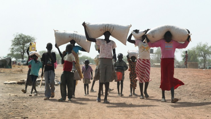 Villagers take from ICRC distribution point oil and seeds
