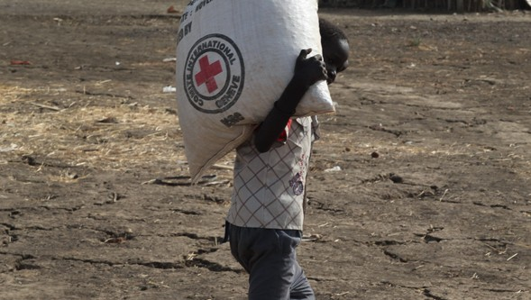 Boy walks on parched land carrying a bag of seed. First rains are due in late April, marking the start of planting season.