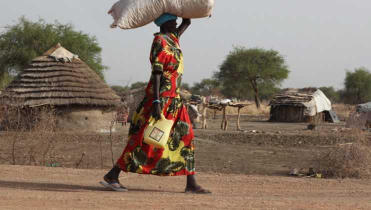 Woman carries oil and seed.  She, like many, lost her crops fleeing fighting in May 2011.