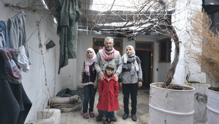 Abu Hani, who lost his wife and son when two rockets hit his home in the Old City of Homs, standing with his three daughters. After two and half years being displaced from their homes, they are now back in their original home, which they repaired with the help of charities