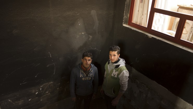 Mohammed stands in his damaged home with his brother Ibrahim. Mohammed tells the story of how he and his brother Ibrahim and their families fled their neighborhood in eastern Mosul when fighting got too intense, expecting to be back within days. When they returned a month and a half later, they found their house destroyed and the area heavily damaged.
