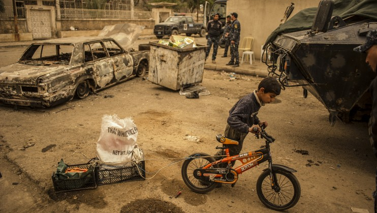 A child transporting gasoline to his house passing by Iraqi soldiers (from the Federal police).