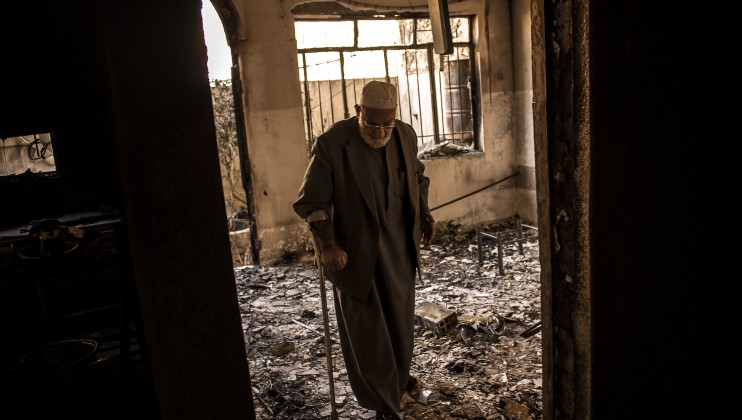 An elderly civilian enters his house, destroyed during the second phase of the military offensive to retake the city from armed groups.