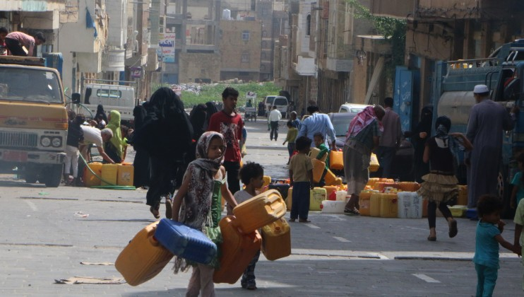 Women and children collect water from a water truck in a besieged area of Taiz.