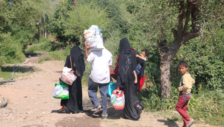 A family uses an unpaved, muddy and mountainous route to leave the besieged areas of Taiz.