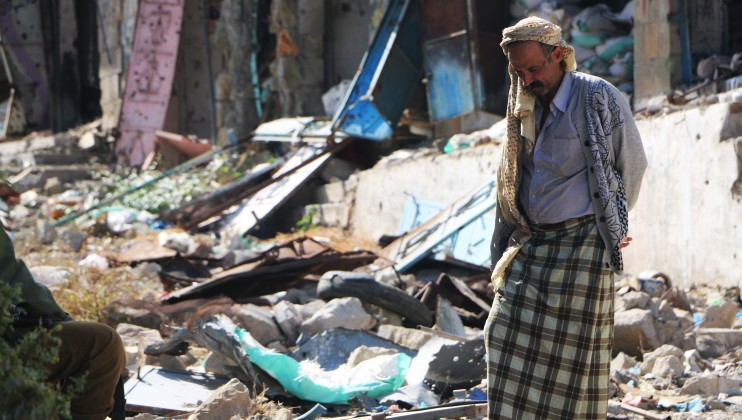An elderly man walks through the damage caused by clashes in his neighborhood.