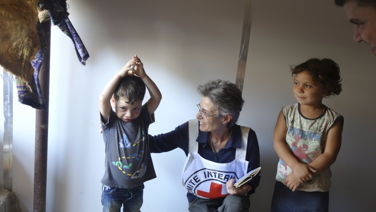 Marianne Gasser, the ICRC's head of delegation in Syria, with two young children displaced from their homes in Aleppo. Their family and many others at this shelter were forced to flee again when fighting affected this area.