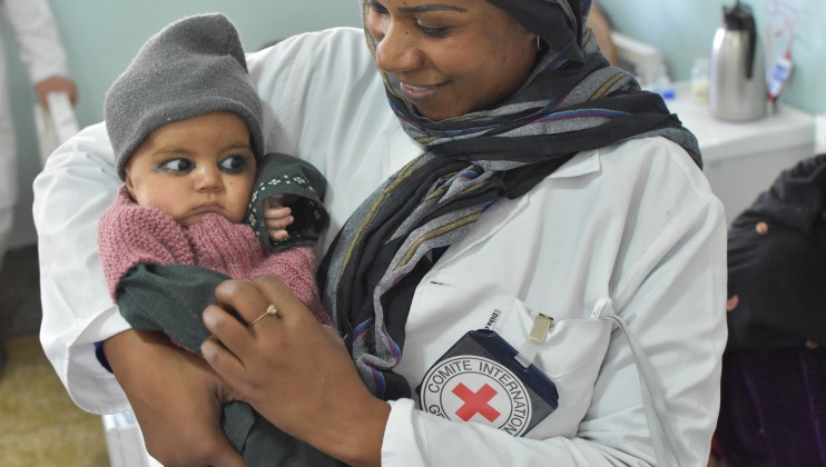 ICRC nurse holds a baby at Mirwais Regional Hospital in Kandahar. Ronan Guillou/ICRC