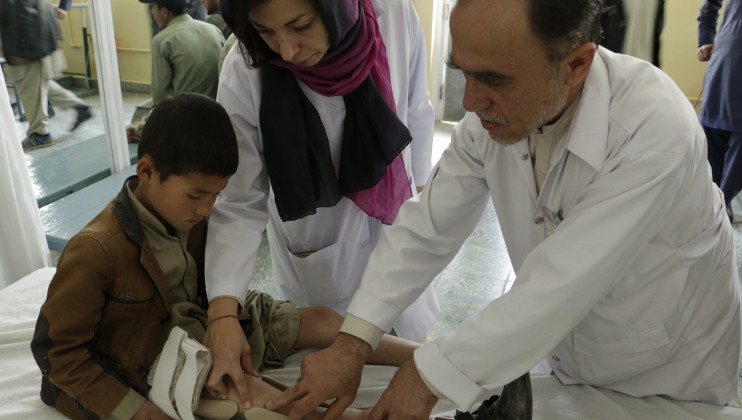 Doctors at the Physical Rehabilitation Centre in Kabul check on the legs of a congenital paralized child. Shamshad Omar/ICRC
