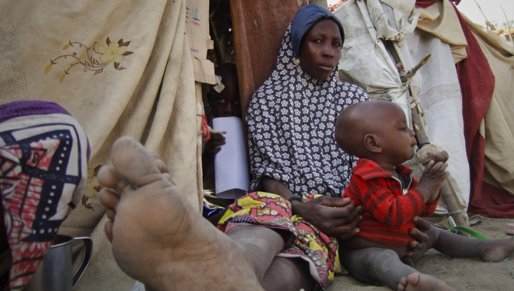 Amina, 25, sits in the shade with her two-year-old Aliyu. Their makeshift hut, though not sturdy, helps guard them from the hot Maiduguri sun. Hassan, her other son peers out from inside the hut.