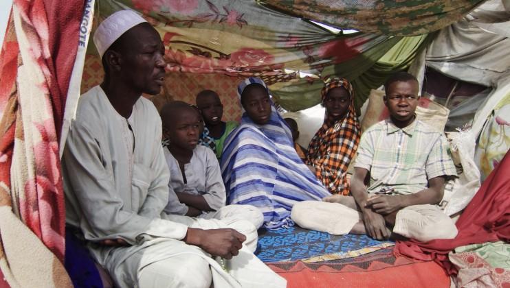 Mohamed Liman (à gauche) et sa famille dans leur abri de fortune dans le camp de déplacés de Teachers Village, à Maiduguri (État de Borno). Mohamed est venu de Cross Kauwa, à plus de 100 km au nord-est de Maiduguri, avec sa mère âgée, sa femme et leurs huit enfants. Le camp est surpeuplé suite aux nombreuses nouvelles arrivées dues à une multiplication des attaques dans l'État. La majeure partie des personnes récemment déplacées se sont installées à Teachers Village, mettant les ressources du camp à rude épreuve.