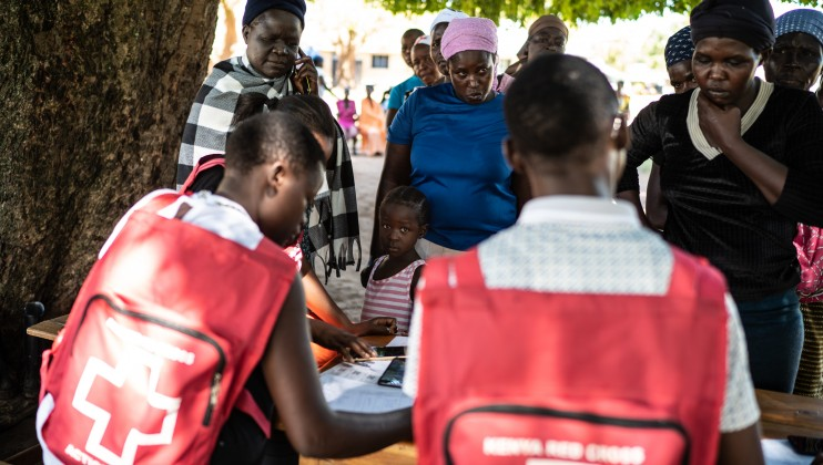 Women and children displaced by flooding register with Kenyan Red Cross for a pop-up medical clinic in Osodo, Homa Bay, Kenya, Tuesday, Dec 17, 2019. Heavy rains have hit Kenya particularly hard this year, killing crops and displacing tens of thousands of people throughout the country. Mackenzie Knowles-Coursin/ICRC