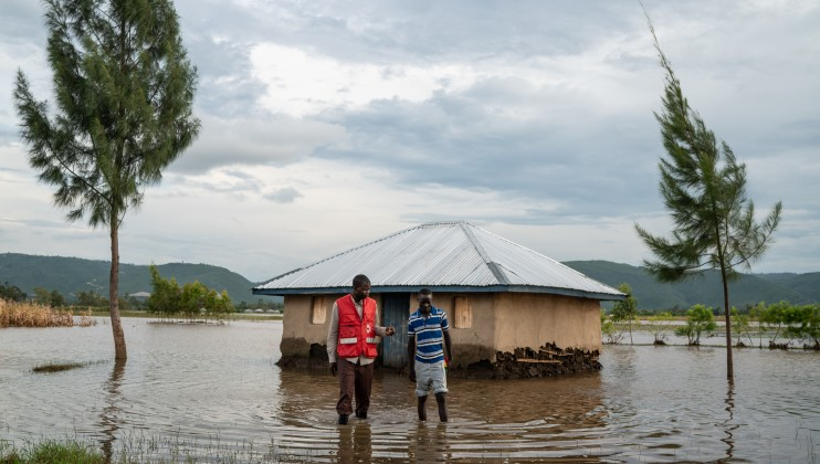 A Kenyan Red Cross worker speaks with a young man after visiting his flooding home in Nyondo, Kisumu County, Kenya, Monday, Dec 16, 2019. Heavy rains have hit Kenya particularly hard this year, killing crops and displacing tens of thousands of people throughout the country. Mackenzie Knowles-Coursin/ICRC