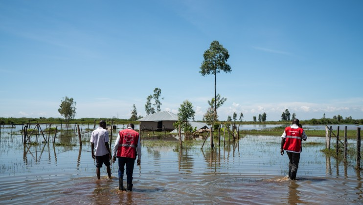 Red Cross workers wade through water to inspect flooded houses in Osodo, Homa Bay, Kenya, Tuesday, Dec 17, 2019. Heavy rains have hit Kenya particularly hard this year, killing crops and displacing tens of thousands of people throughout the country.  Mackenzie Knowles-Coursin/ICRC