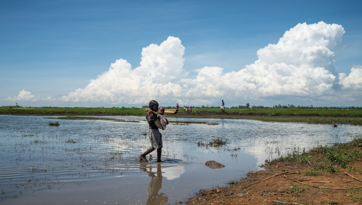 A boy carries his younger sister through some of the flood waters that have inundated much of Kisumu County, Kenya, Monday, Dec 16, 2019. Heavy rains have hit Kenya particularly hard this year, killing crops and displacing tens of thousands of people throughout the country. Mackenzie Knowles-Coursin/ICRC