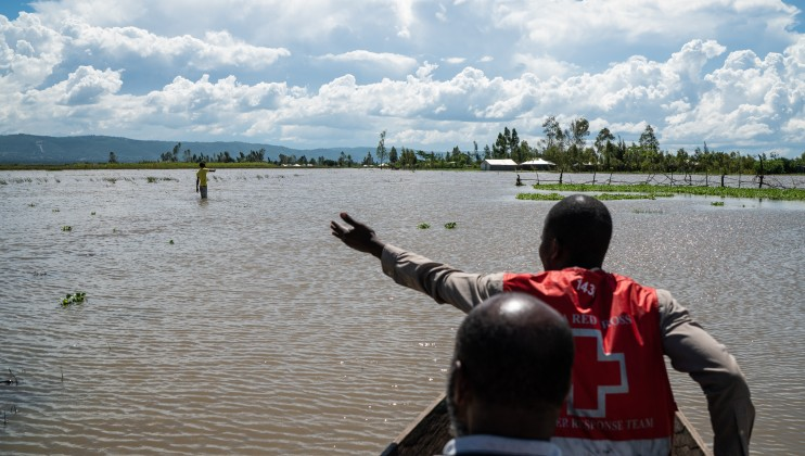 A Kenyan Red Cross worker points out crop land that has been devastated by recent flooding in West Nykach, Kisumu County, Kenya, Monday, Dec 16, 2019. Heavy rains have hit Kenya particularly hard this year, killing crops and displacing tens of thousands of people throughout the country. Mackenzie Knowles-Coursin/ICRC