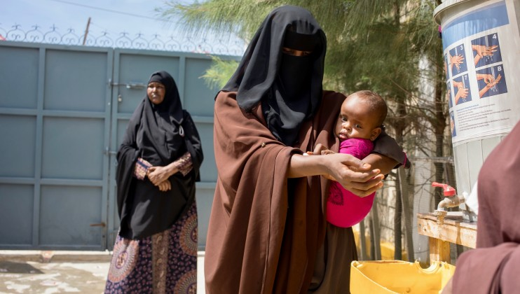 Handwashing stations have been setup across all Somali Red Crescent Socity (SRCS) clinics in South and Central Somalia. A mother washese her hands at the entrance of the SRCS clinic. ICRC/Ismail Taxta