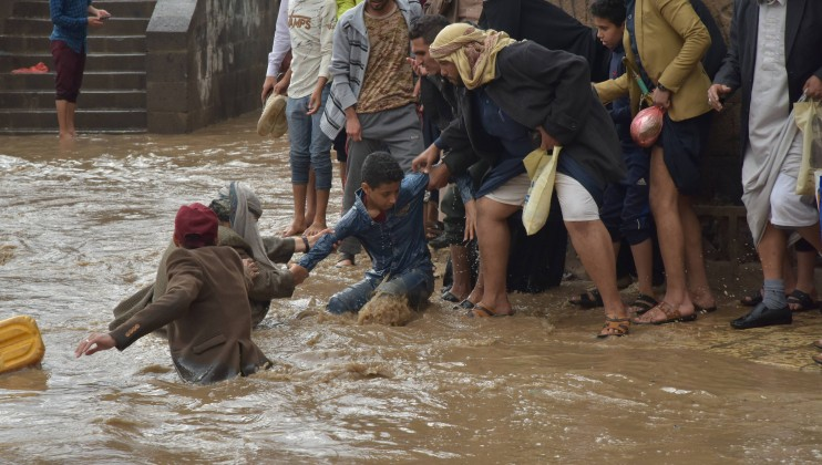 People help rescue a child during the floods in Sana'a city. © Ali Alsonaidar