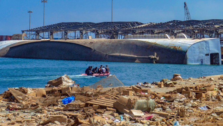 Beirut Port, the rear view of the ship that has been turned upside down, and rescuers searching.