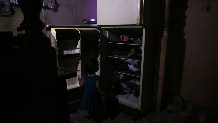 A girl is looking at a fridge without power used as a shoe storage space