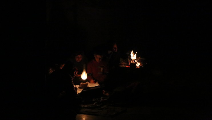 A mother of six is helping two of her children to study during a blackout