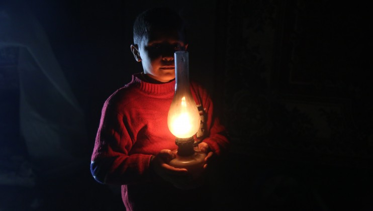 A young boy is holding an oil lamp that is used for studying once the power cuts