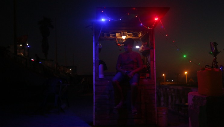 A street vendor next to his stand during the night in Gaza which us lit by LED lights.
