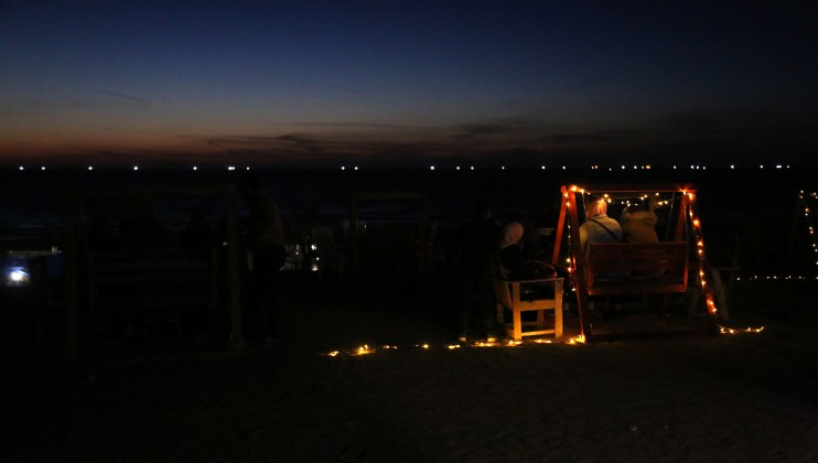 A group of people is sitting at the beach during the night in Gaza