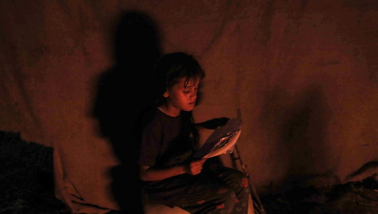 A girl is studying during without electrical lighting